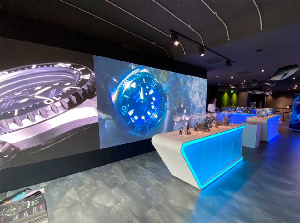 Seiko Taucheruhren, gezeigt auf einer LED Wand, mit Ozeaneum Ausstellungsobjekten davor